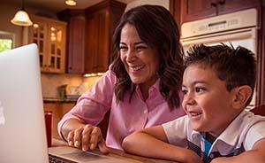 Happy Mom and Cub Scout using laptop