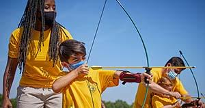 Cub Scout boy in face covering doing archery