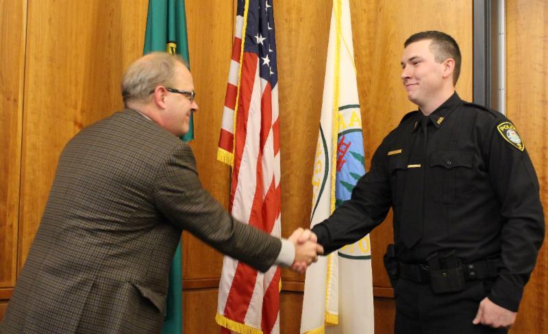 City Attorney Steve Peiffle congratulates new Officer Tim Zachman