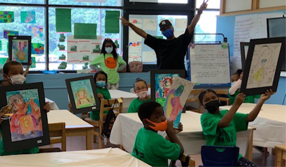 Image: Students in a classroom hold up drawings while Jerome LaMaar stands in background with arms stretched out.