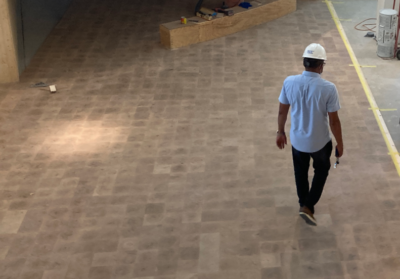 Image - A man walks across newly installed wood tile flooring