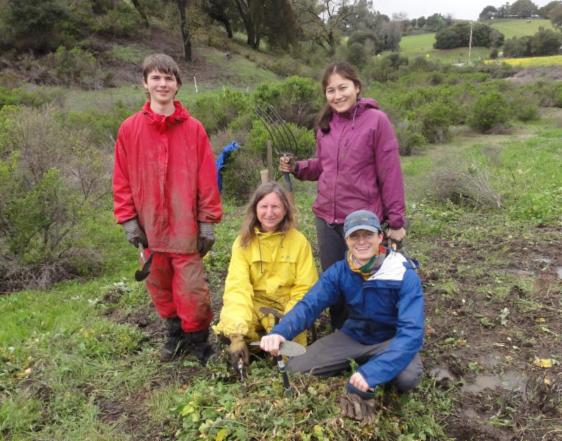 four people in bright raincoats hold weeding tools and smile