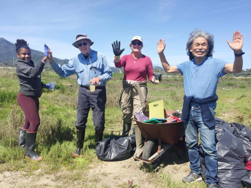 Four volunteers in workboots cheer around a pile of garbage bags and a full wheelbarrow