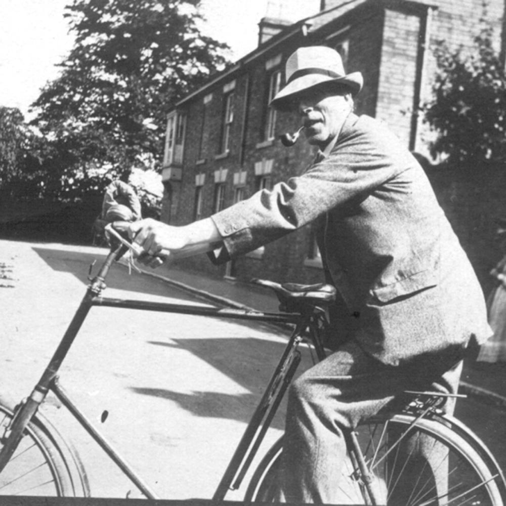 Cecil Sharp, a middle-aged man wearing a suit and a hat, climbs aboard a bicycle on an empty street. He is holding a pipe in his mouth and looking toward the camera, but his eyes are in the shadow of his hat.