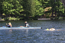 boat with two individuals and person swimming