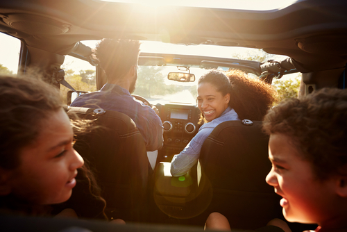 Happy family on a road trip in their car_ rear passenger POV