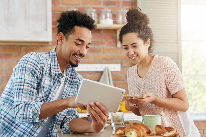 People family online shopping concept. Young affectionate couple going to buy new accomodation look at advertisments in internet use modern tablet computer preparre lunch together. Home interior