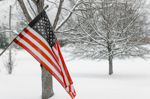 American flag with winter snow background. Celebrate National USA Holiday and patriotic pride.