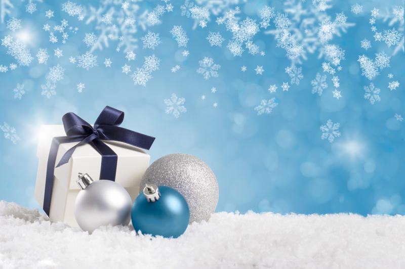 Christmas gift wrapped with blue ribbon with silver balls on white snow. Little christmas present on snow with copy space on blue background. Blue and silver xmas decoration with copyspace.
