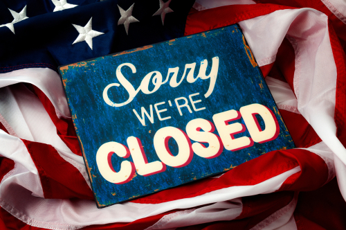 Government shutdown_ Washington is broken_ political deadlock and partisan politics concept theme with a sorry we re closed sign and the American flag