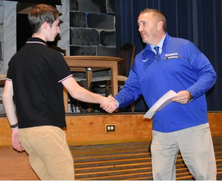 Fall sports award picture of student receiving an award.