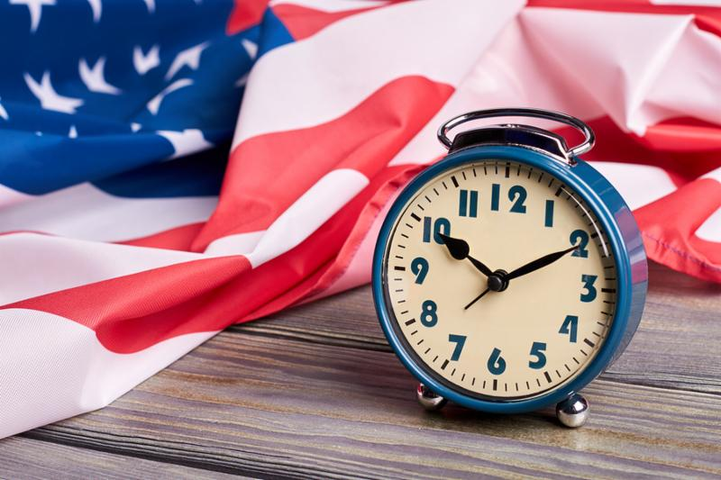 USA flag and alarm clock. Crumpled flag of United States of America and mechanical alarm clock on wooden surface close up.