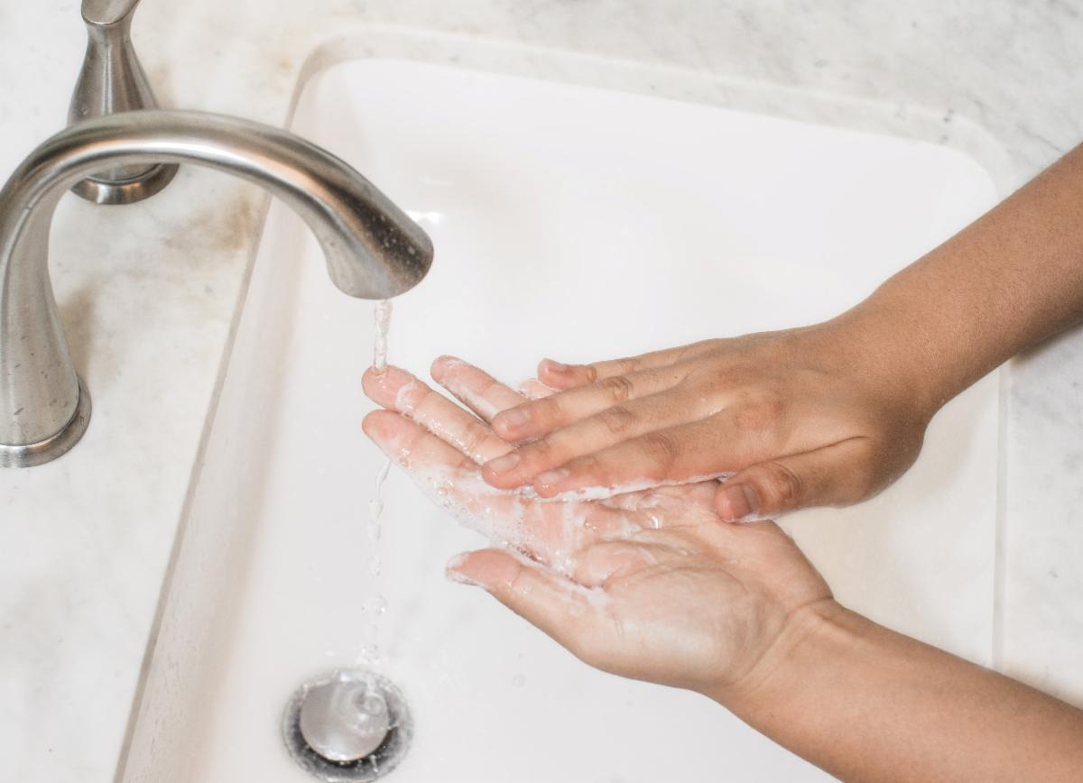 person washing hands in sink