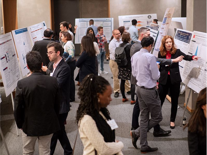 Attendees at the PHS Conference engage in a poster presentation in December 2019.