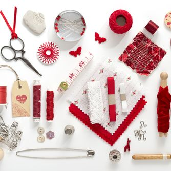 a collection needle work accessories in red on white background