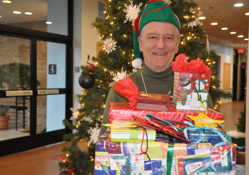 Secret Santa elf with gifts in front of tree