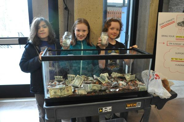 Kids in front of tank of coins