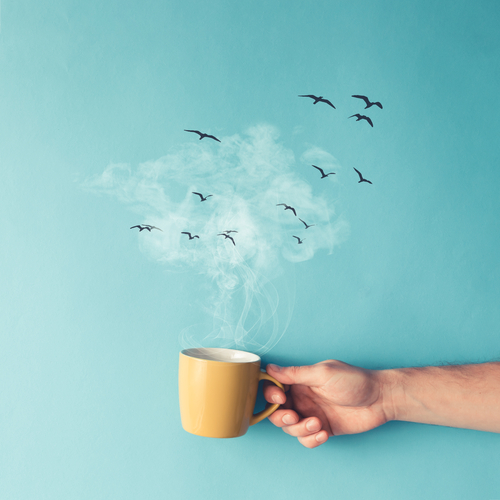 Coffee cup with steam_ clouds and birds. Coffee concept. Flat lay.