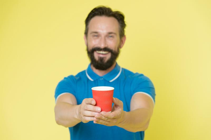 Guy beard and mustache holds paper cup of tea or coffee. Offer drink to you. Trainer experienced man care about water balance. Share and generosity concept. Have a sip. Take this if you want to drink.