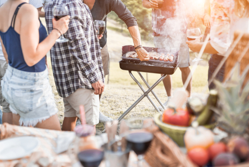 Group of people people having picnic barbecue in nature outdoor - Happy friends cooking meat and drinking wine in weekend summer day - Family_ food and friendship concept - Focus on bbq grill meat