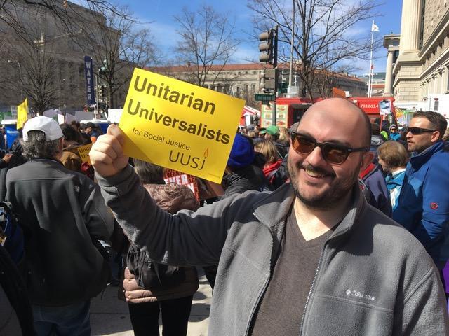 a demonstrator holding UUSJ sign