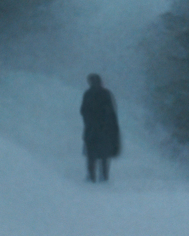 man in silhoette in snow