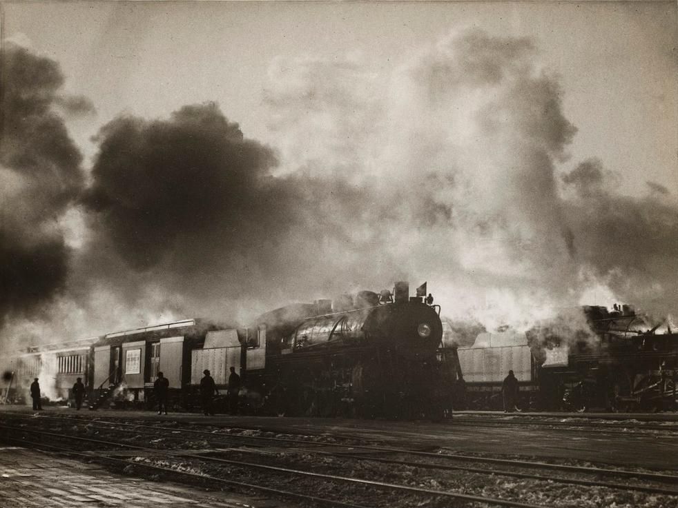 train coming down tracks with smoke