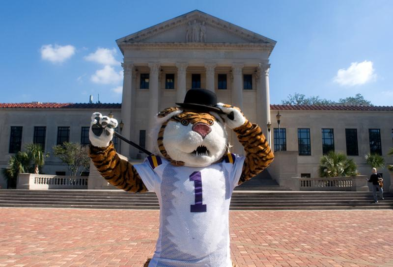 A costumed tiger wears a black hat and holds a cane in front of the LSU Law Center