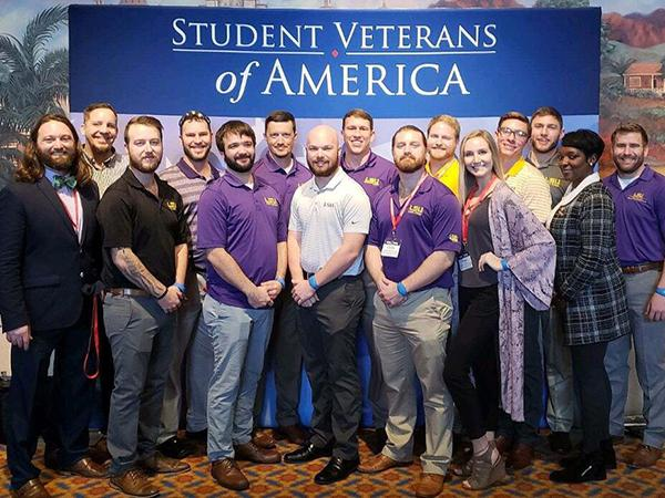A group of student veterans poses for a photo with the Student Veterans of America banner in the background