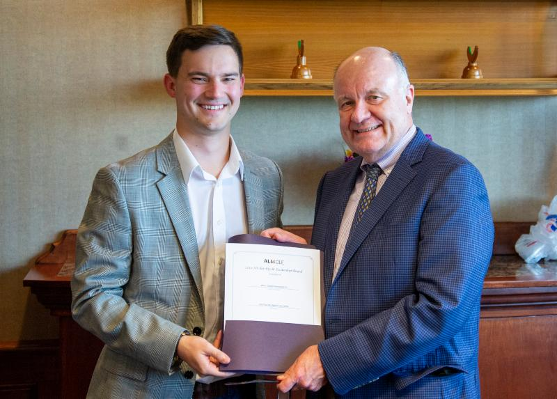 Two males in suits smile and hold a certificate