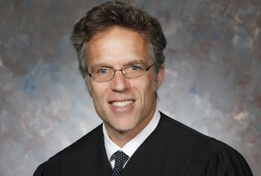 A headshot photo of a man wearing a judge's robe