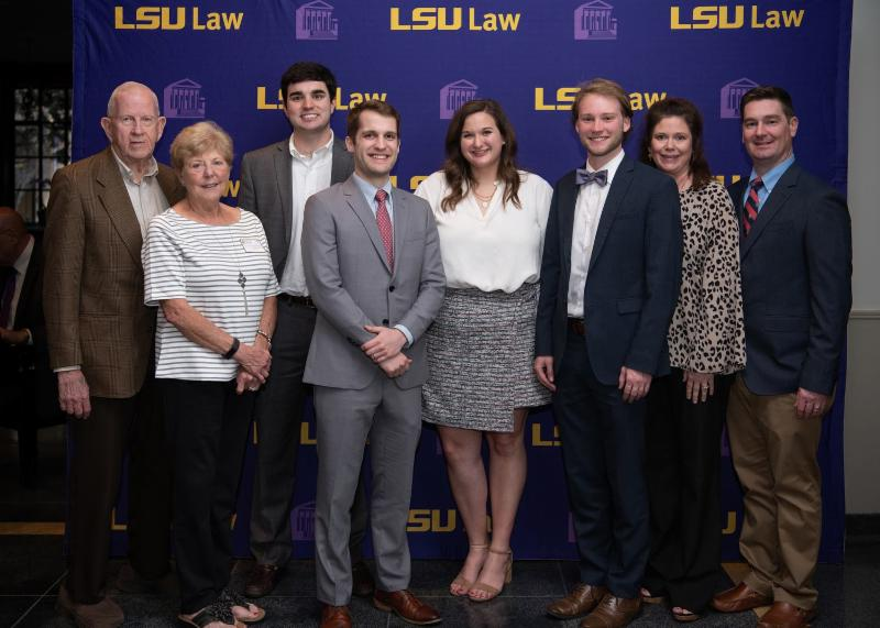 A group of people stand for a photo with the LSU Law logo backdrop in the background