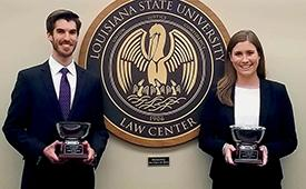 A male and female pose in front of the LSU Law Center seal with trophies