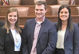 Two female and one male students wearing suits pose for a photo with a courtroom in the background