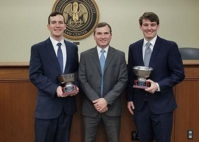 Two male students wearing suits and holding silver trophies pose for a photo with an older male in a suit