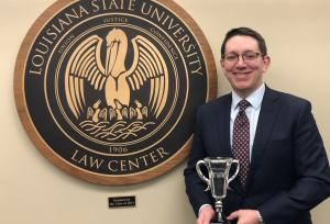 A male student holds a crystal trophy while standing next to the LSU Law Center seal