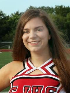 Sydney Johnson, a brunette teenager, smiles in her cheerleading uniform. The picture was taken outside in front of trees.