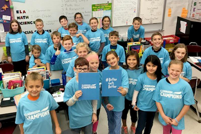 Mrs. Eichelberger's class smiles and wear their blue classroom champions shirts.