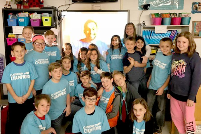 Mrs. Eichelberger poses with her class, in background is Olympian Chris Mazdzer on  screen behind them via Google Hangout