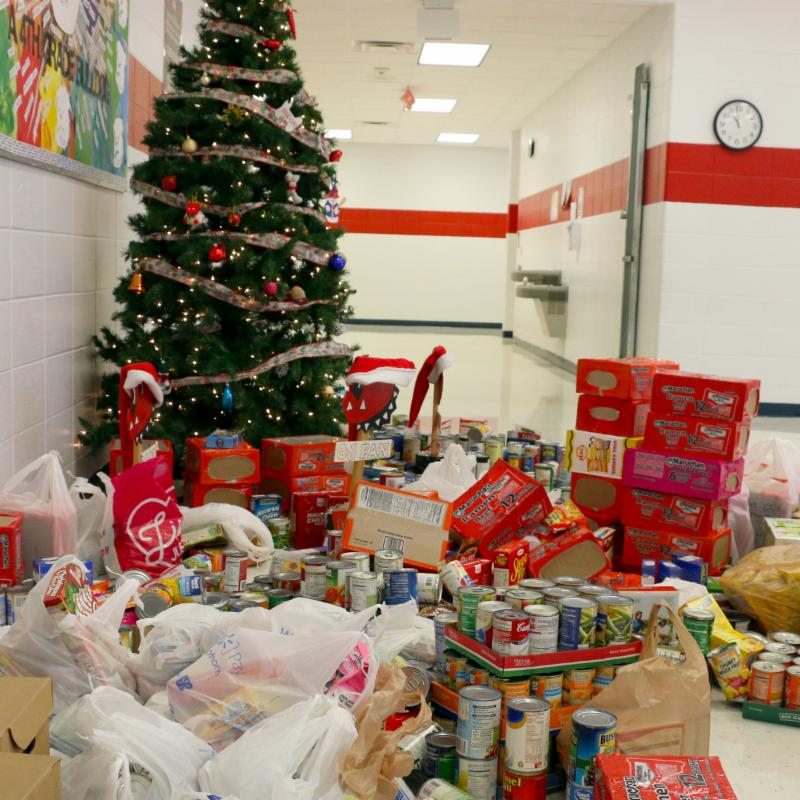 A Christmas tree stands in the hallway of the intermediate bulding. All around it for at least 6 feet in every direction, non perishable foods are stacked.
