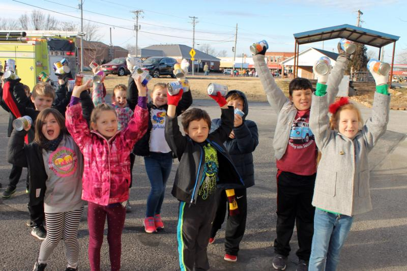 Outdoor in a parking lot, a group of small children dressed warmly smile and hold food cans above their heads.