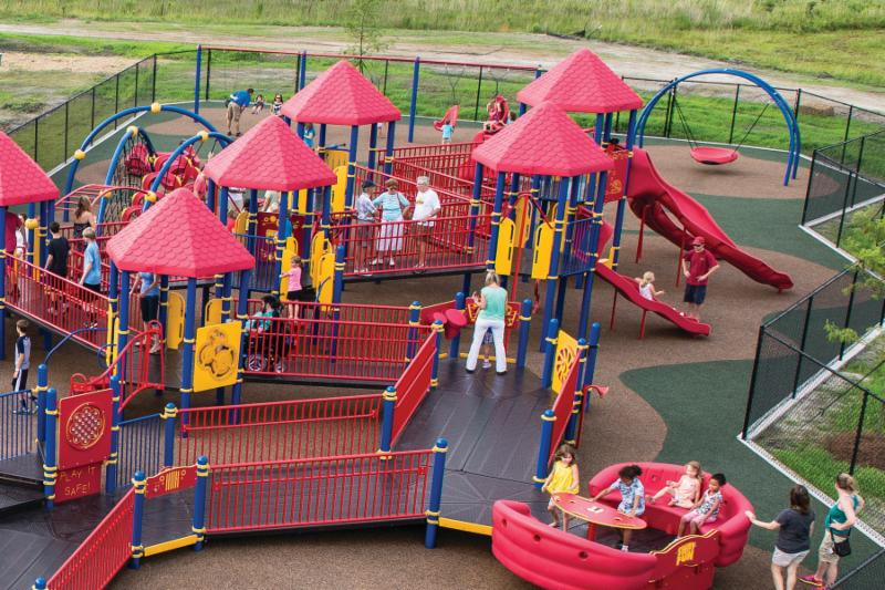 A colorful playground structure with children and adults playing is pictured from above. All parts are accessible and low to the ground. Surfacing is handicap accessible outdoor rubber.