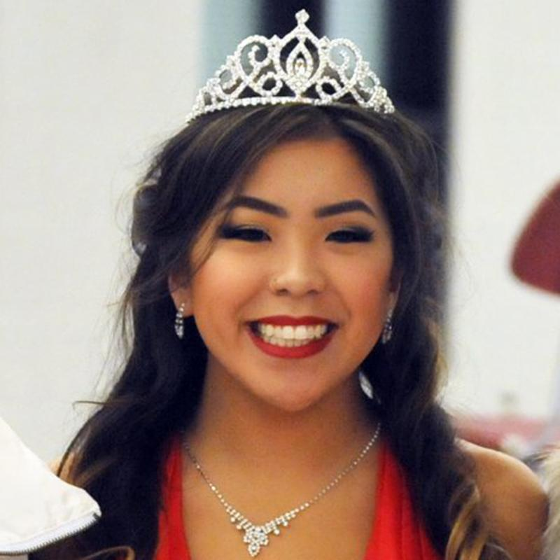 Cana Sluder wears crown, jewled necklace and red dress smiling after homecoming coronation
