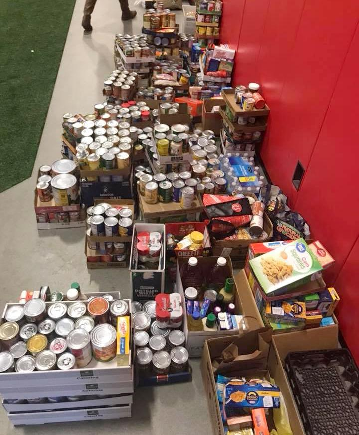 Dozens of boxes of non perishables are gathered on a floor