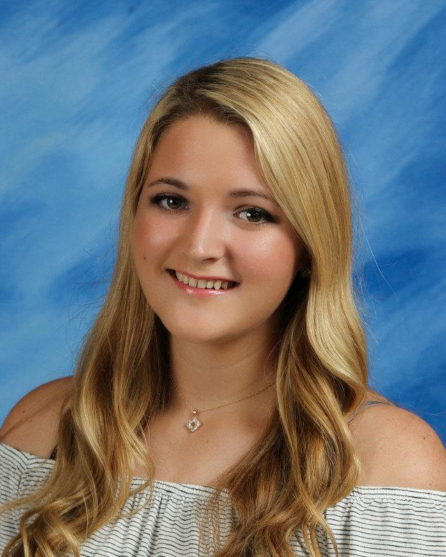 Kaylie Hulette smiles in a yearbook photo with a blue background. She has long wavy blonde hair.