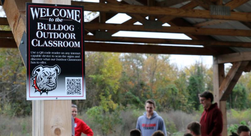 A close up of the structure with sign saying Welcome to the Bulldog Outdoor Classroom.