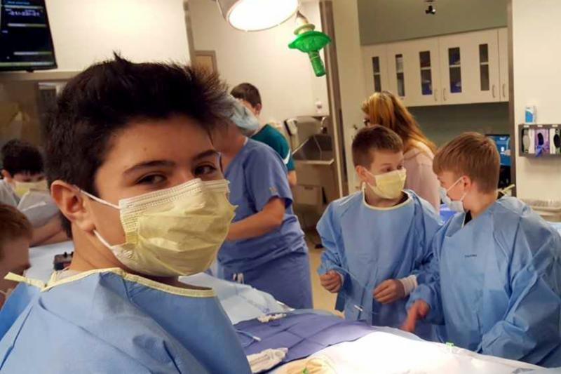 A group of 7th grade boys are in a hospital room, by a hospital bed in blue surgical gowns and face masks. In the background there are nurses helping.