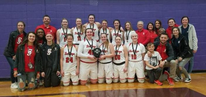 The girls basketball team wears medals and holds trophy and poses in gym with team managers, coaches and friends