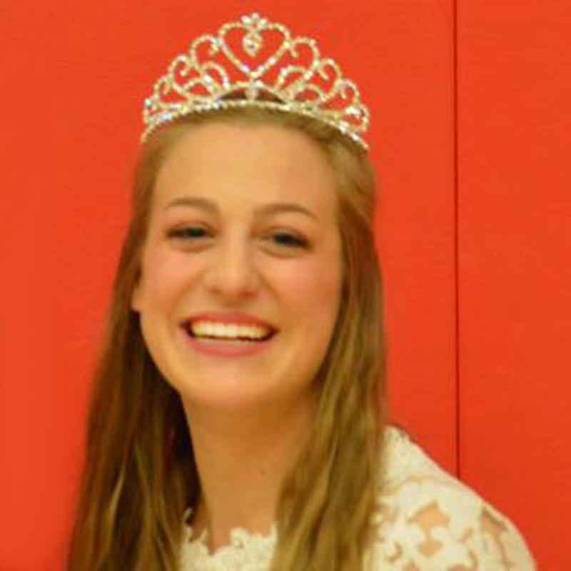 Senior Kate Dreiling wears crown and lace white dress, smiling after being crowned at wrestling homecoming