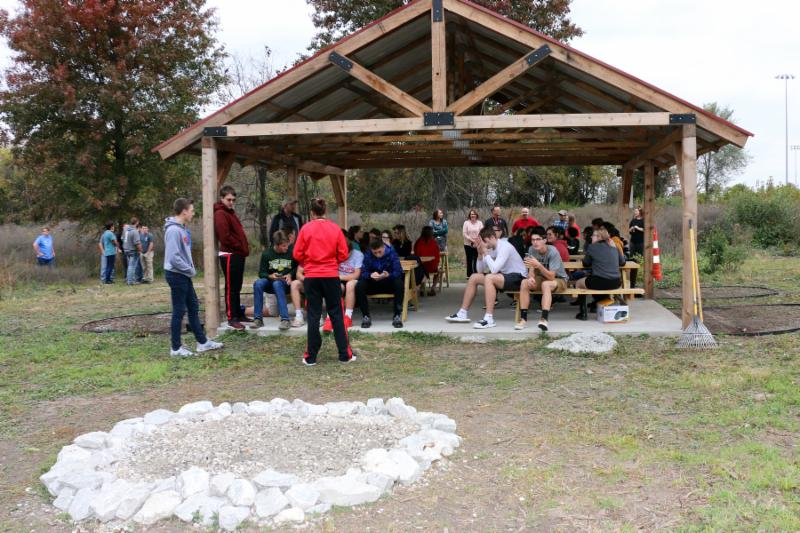 Students sit outdoors in a wild area under a wooden structure with tin roof, cement floor, and wooden picnic tables. There is also a stone fire pit.